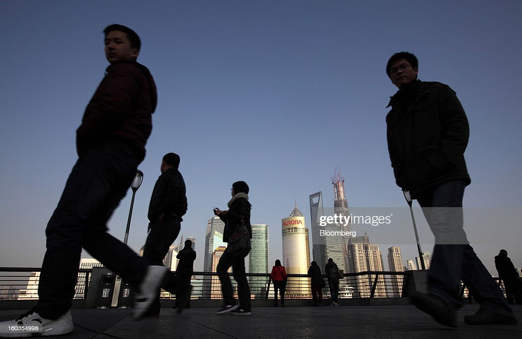Pedestrians walk along the Bund waterfront as commercial buildings stand in the background in Shanghai, China, on Monday, Jan. 28, 2013. China's economic growth accelerated for the first time in two years as government efforts to revive demand drove a rebound in industrial output, retail sales and the housing market. Photographer: Tomohiro Ohsumi/Bloomberg via Getty Images