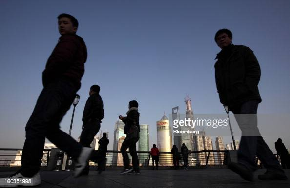 Pedestrians walk along the Bund waterfront as commercial buildings stand in the background in Shanghai China on Monday Jan 28 2013 China's economic...