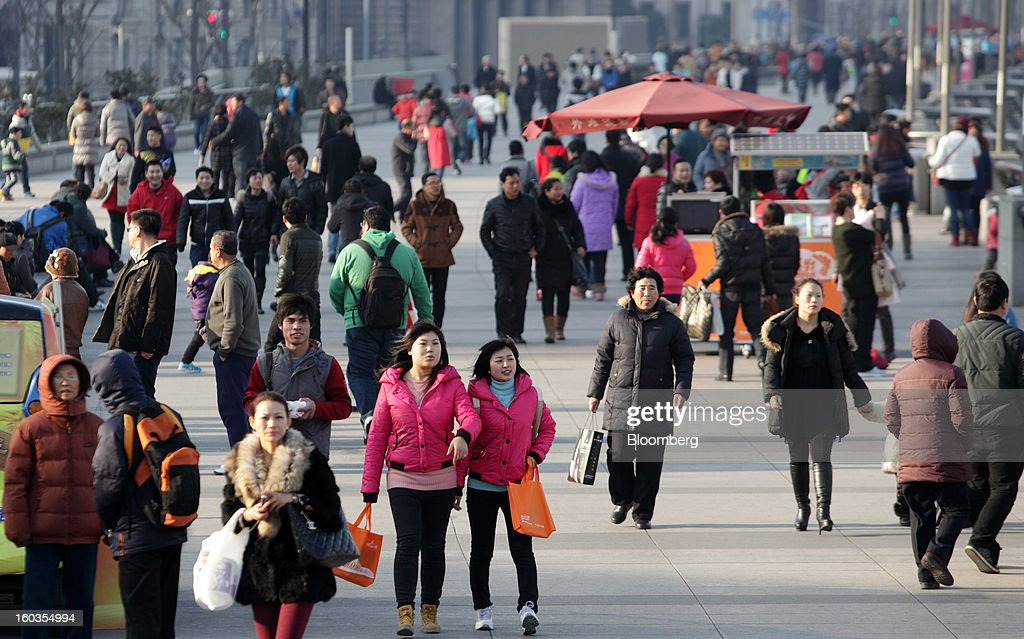 Pedestrians walk along the Bund waterfront in Shanghai, China, on Monday, Jan. 28, 2013. China's economic growth accelerated for the first time in two years as government efforts to revive demand drove a rebound in industrial output, retail sales and the housing market. Photographer: Tomohiro Ohsumi/Bloomberg via Getty Images