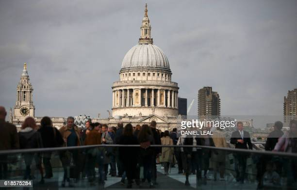 Pedestrians walk along the Millennium Bridge with St Paul's Cathedral in the background in London on October 27 2016 Britain's economy won a double...
