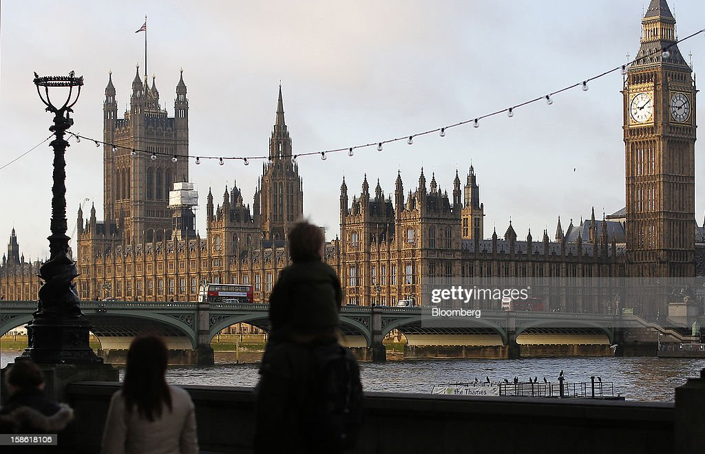 Pedestrians walk along the River Thames opposite the Houses of Parliament and Big Ben clocktower, right, in London, U.K., on Friday, Dec. 21, 2012. Britain's economy expanded less than previously estimated in the third quarter and the budget deficit unexpectedly widened in November, complicating Prime Minister David Cameron's attempts to bolster the recovery. Photographer: Simon Dawson/Bloomberg via Getty Images