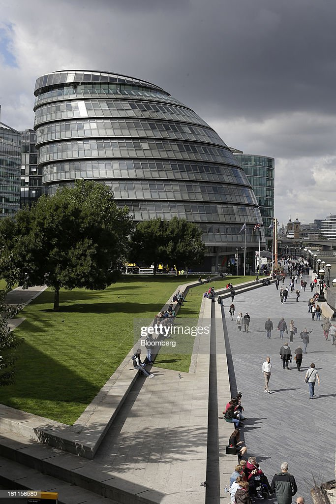 Pedestrians walk along the south bank of the River Thames as City Hall stands beyond in London, U.K., on Wednesday, Sept. 18, 2013. U.K. commercial real estate values rose for the fourth straight month in August, led by office buildings and warehouses, Investment Property Databank Ltd. said. Photographer: Matthew Lloyd/Bloomberg via Getty Images