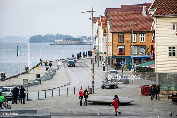Pedestrians walk along the waterside past old buildings near the dock and port area in Stavanger Norway on Tuesday March 4 2014 Norwegians debt...