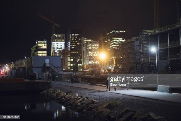 Pedestrians walk along the waterside towards residential and commercial buildings in the Barcode development area at night in Oslo Norway on...