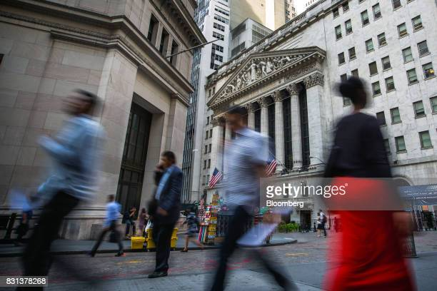 Pedestrians walk along Wall Street near the New York Stock Exchange in New York US on Monday Aug 14 2017 US stockindex futures advanced and...