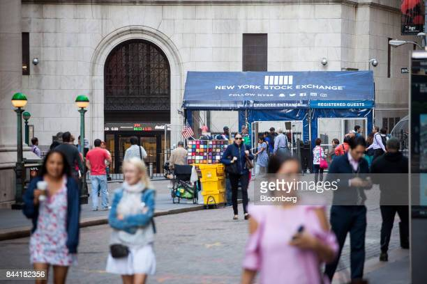 Pedestrians walk along Wall Street near the New York Stock Exchange in New York US on Friday Sept 8 2017 The dollar fell to the weakest in more than...