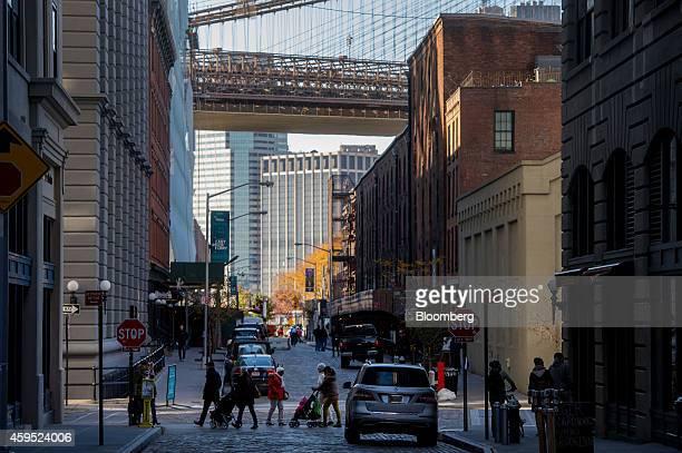 Pedestrians walk along Water Street under the shadow of the Brooklyn Bridge in the DUMBO neighborhood in the Brooklyn borough of New York US on...