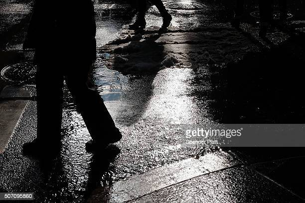 Pedestrians walk along wet and slushy streets in Manhattan as warmer temperatures melt snow from a historic weekend blizzard on January 27 2016 in...