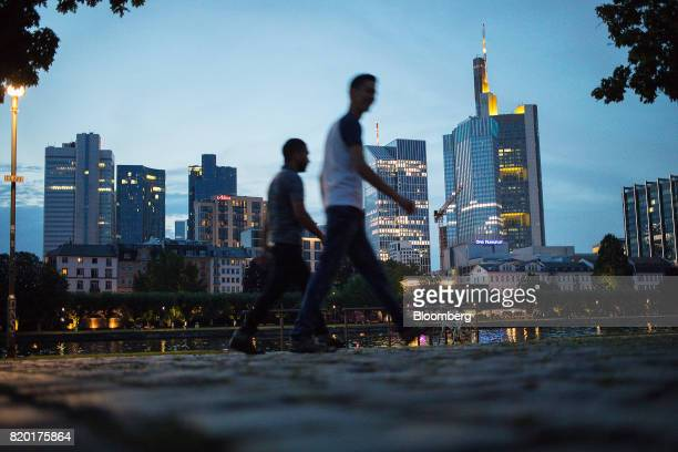 Pedestrians walk alongside the River Main as skyscrapers stand beyond at dusk in Frankfurt Germany on Wednesday July 19 2017 Frankfurt has emerged as...