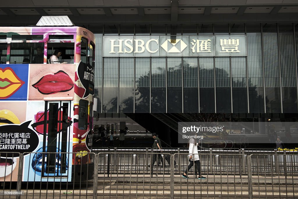 Pedestrians walk and a tram passes in front of the HSBC Holdings Plc headquarters building in Hong Kong, China, on Saturday, Feb. 13, 2016. HSBC's board will meet on Sunday to decide whether to shift its headquarters from London, according to two people with knowledge of the decision. Photographer: Xaume Olleros/Bloomberg via Getty Images