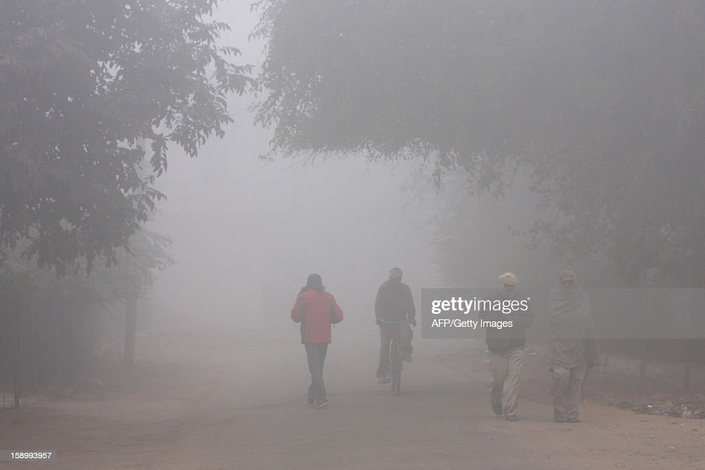 Pedestrians walk and cycle along a road during a cold and foggy morning in Allahabad on January 5, 2013. Temperatures have dropped across northern India, with capital New Delhi recording its coldest day in 44 years on January 3. AFP PHOTO/ Sanjay KANOJIA