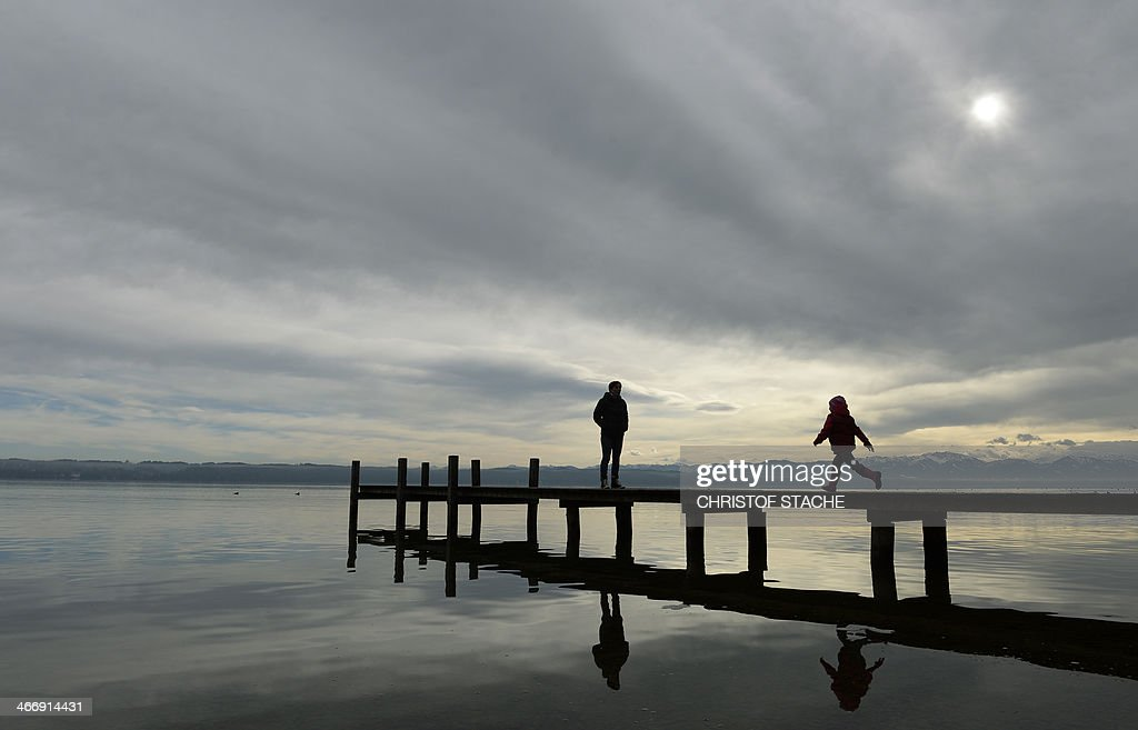Pedestrians walk at a rack near the lake Starnberger See in Tutzing, southern Germany, during winter weather and temperatures by the freezing point on February 5, 2014. Meteorologists forecast changeable weather during the week. AFP PHOTO/CHRISTOF STACHE