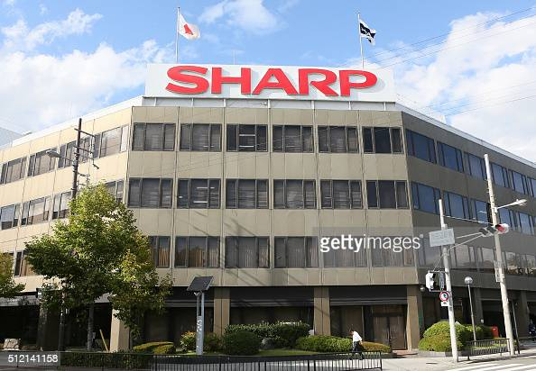 Pedestrians walk before the headquarters of Japan's electronics company Sharp in Osaka western Japan on February 25 2016 Sharp accepted a...