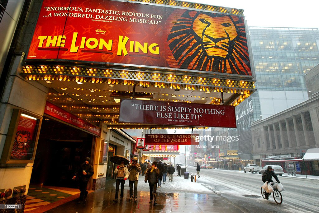 Pedestrians walk beneath a sign for the musical 'The Lion King' March 6, 2003 in New York City. About 325 Broadway theater musicians are set to go on strike tonight at midnight unless an agreement on orchestra size can be reached.
