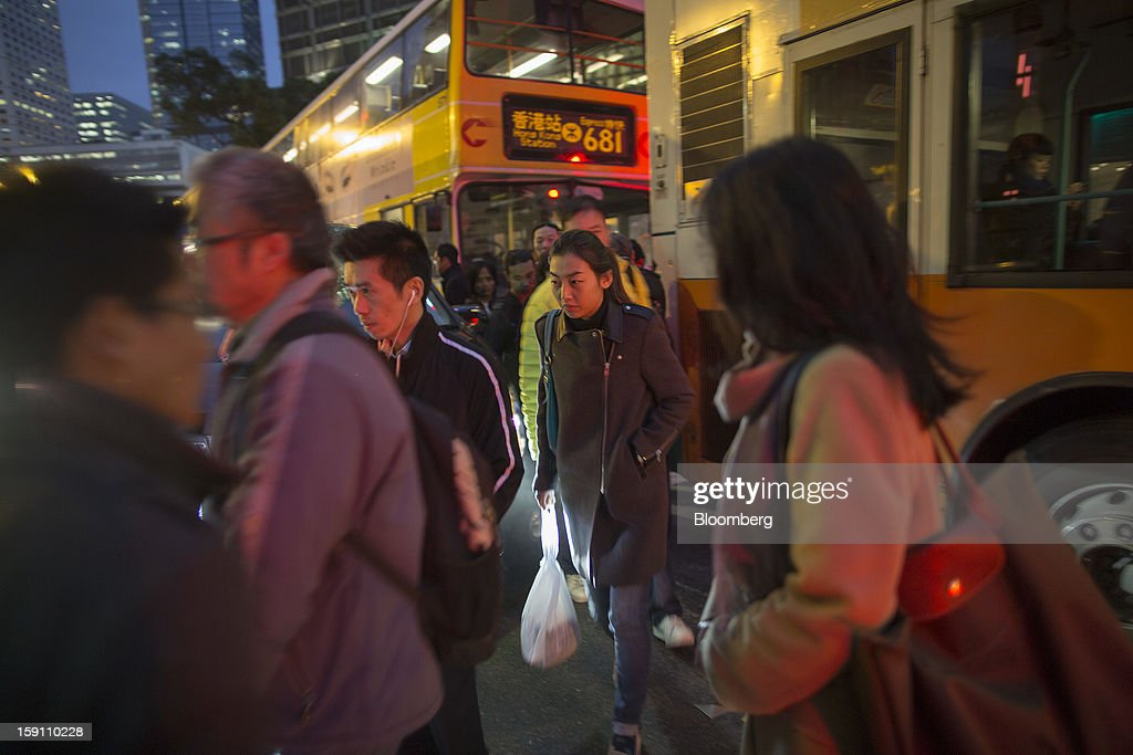 Pedestrians walk between buses as they cross a road in the central business district of Hong Kong, China, on Friday, Jan. 4, 2013. Chief Executive Leung Chun-ying, who has been buffeted by student protests and low popularity since taking office on July 1, has pledged to tackle Asia's biggest wealth gap as the division between poor and rich widened to its worst level since at least 1971. Photographer: Jerome Favre/Bloomberg via Getty Images