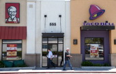 Pedestrians walk by a KFC and a Taco Bell restaurant on July 2 2014 in San Rafael California Fastfood giants McDonald's Taco Bell and KFC all ranked...