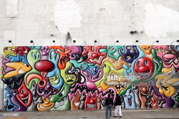 Pedestrians walk by a new mural by the graffiti artist Kenny Scharf on November 30 2010 in New York City The mural which is located on Bowery Street...