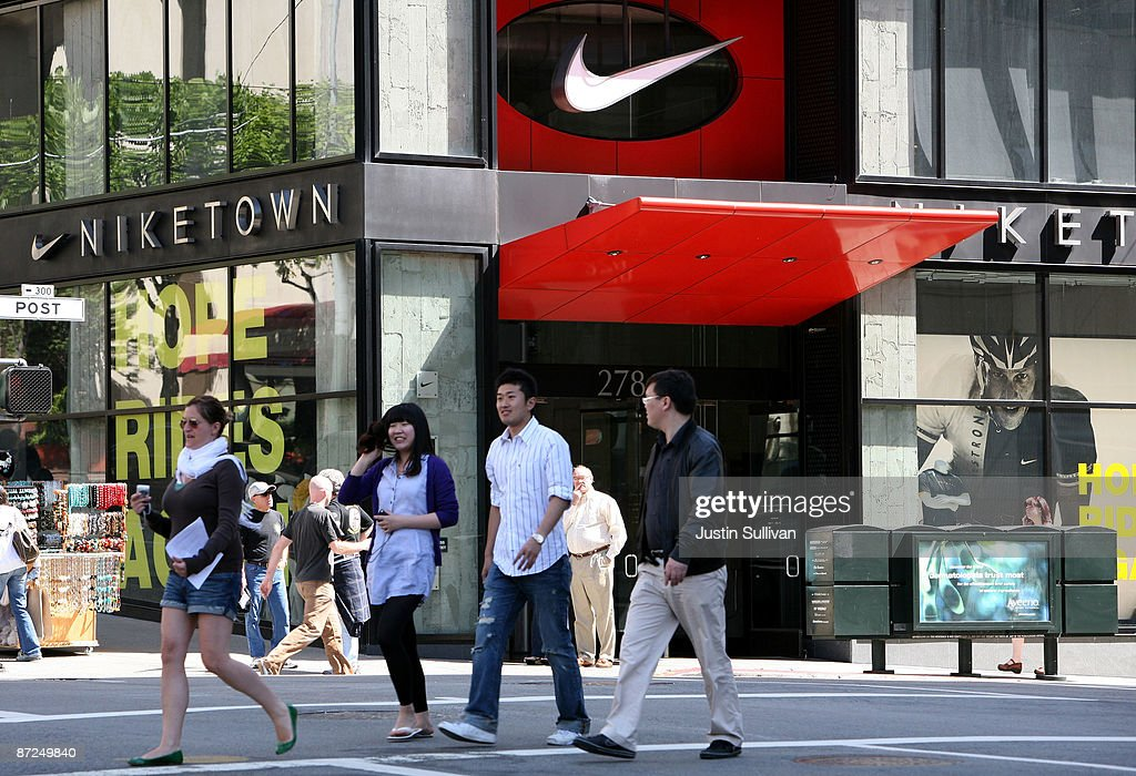 Pedestrians walk by a NikeTown store May 15 2009 in San Francisco California Athletic shoe and sports apparel maker Nike Inc announced that it will...