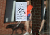 Pedestrians walk by a now hiring sign posted in the window of a business on November 7 2014 in San Rafael California According to a US labor...