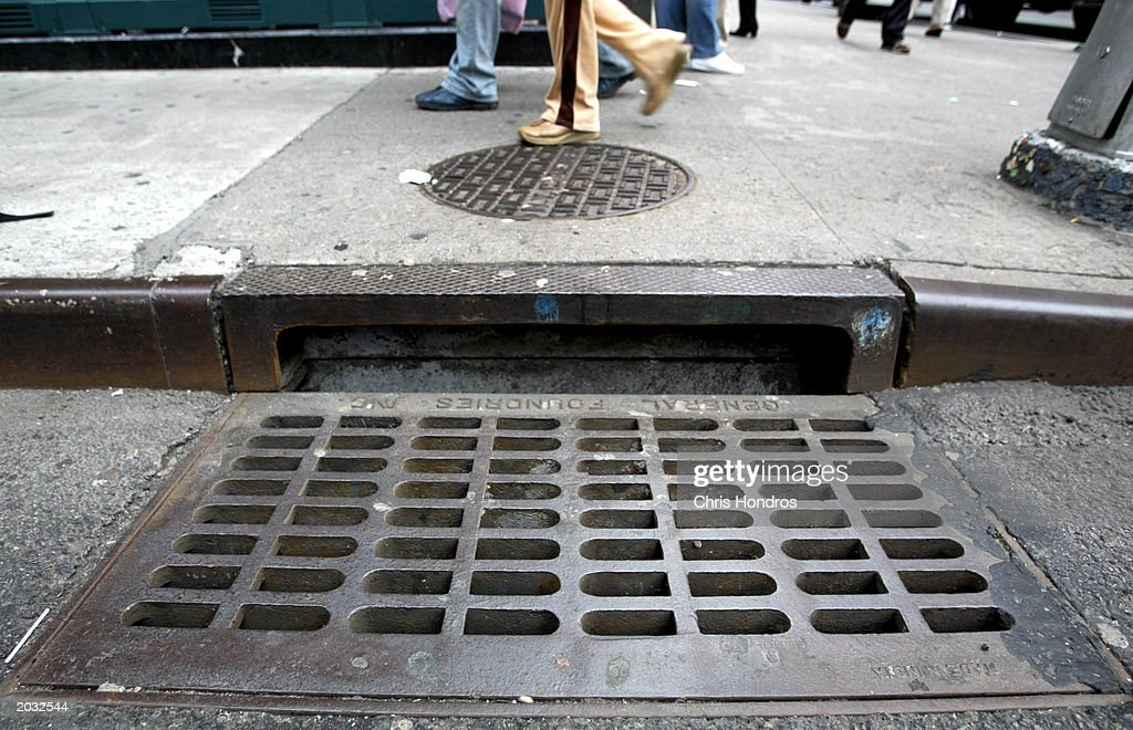 Pedestrians walk by a sewer grate May 27 2003 in New York City Last year the US Environmental Protection Agency sought to require the nation's 15000...