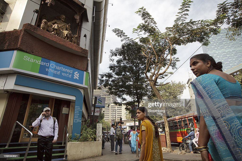 Pedestrians walk by a Standard Chartered Plc bank branch in Mumbai, India, on Wednesday, Jan. 16, 2013. India's financial system has been made vulnerable by a deterioration in bank assets and a lack of capital as the economy slowed, according to the International Monetary Fund. Photographer: Kuni Takahashi/Bloomberg via Getty Images