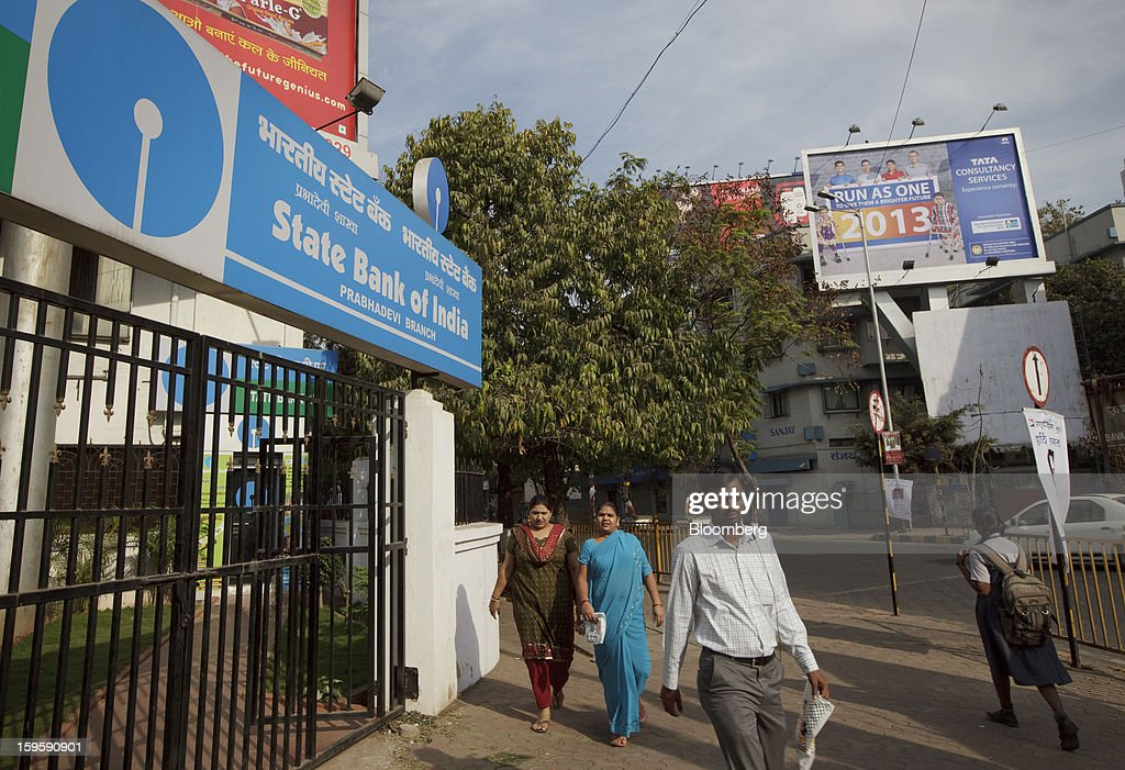 Pedestrians walk by a State Bank of India bank branch in Mumbai, India, on Wednesday, Jan. 16, 2013. India's financial system has been made vulnerable by a deterioration in bank assets and a lack of capital as the economy slowed, according to the International Monetary Fund. Photographer: Kuni Takahashi/Bloomberg via Getty Images