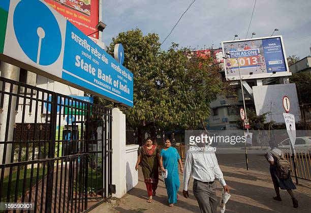 Pedestrians walk by a State Bank of India bank branch in Mumbai India on Wednesday Jan 16 2013 India's financial system has been made vulnerable by a...