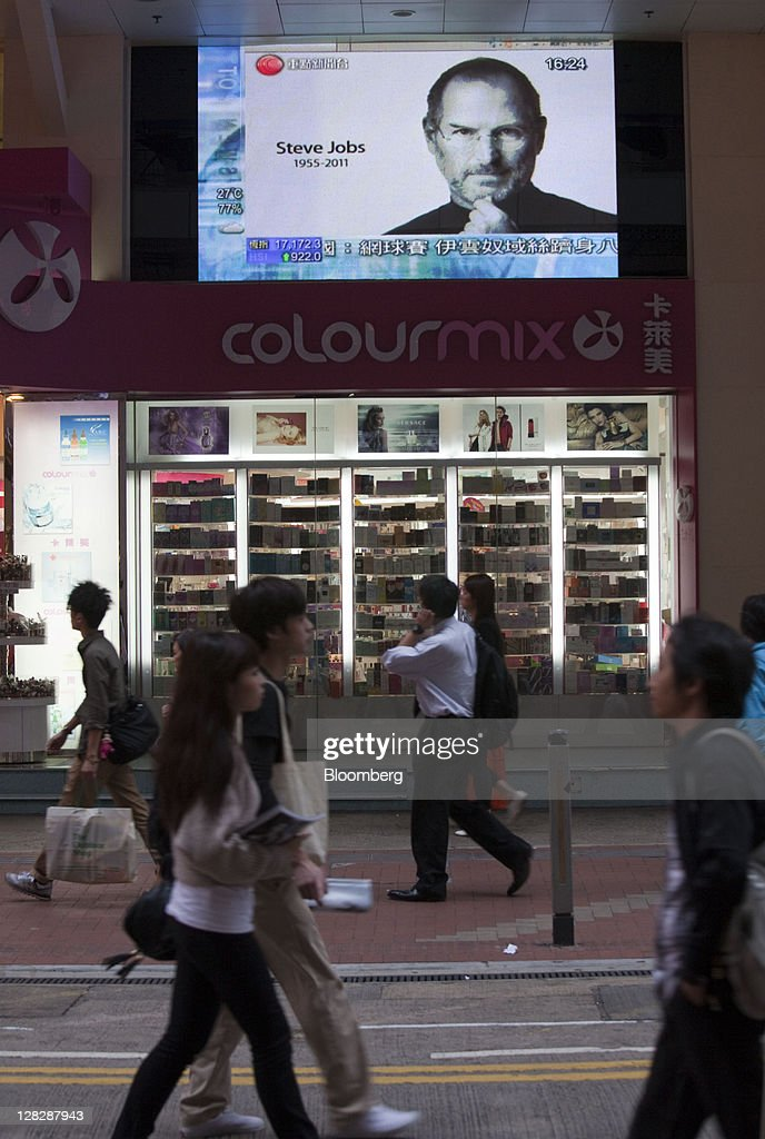 Pedestrians walk by a television screen reporting the death of Steve Jobs, co-founder and former chief executive officer of Apple Inc., in Hong Kong, China, on Thursday, Oct. 6, 2011. Jobs, who built the world's most valuable technology company by creating devices that changed how people use electronics and revolutionized the computer, music and mobile-phone industries, died on Oct. 5. He was 56. Photographer: Jerome Favre/Bloomberg via Getty Images