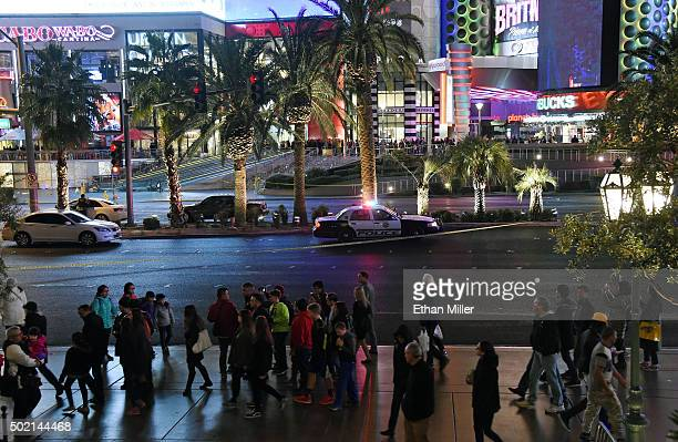 Pedestrians walk by across from Planet Hollywood Resort Casino after police shut down all vehicle traffic on the Las Vegas Strip after a car crashed...