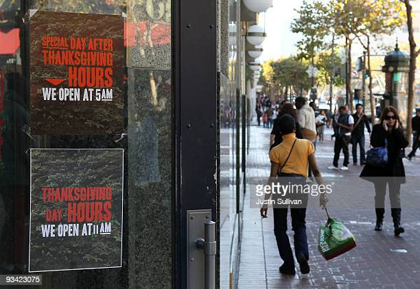 Pedestrians walk by an advertisement for Thanksgiving Day hours at an American Eagle store November 25 2009 in San Francisco California As the...