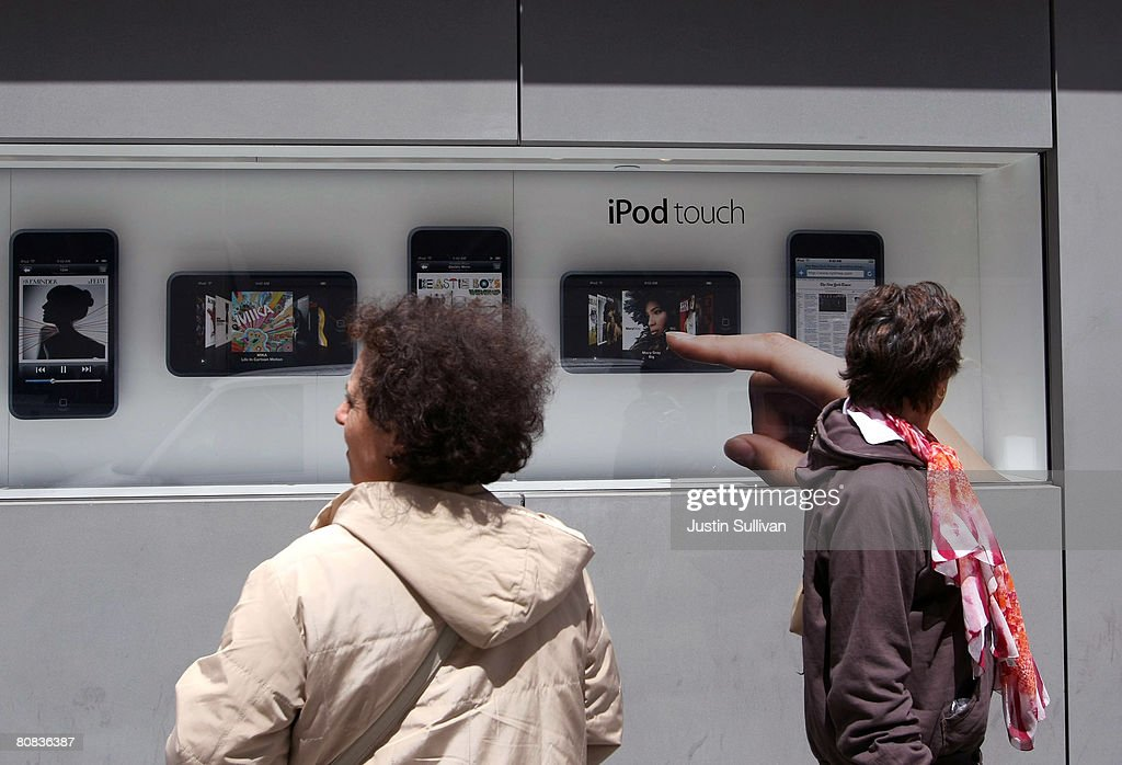 Pedestrians walk by an Apple iPod Touch window display at an Apple Store April 23, 2008 in San Francisco, California. Apple reported its second quarter profits today as $1.05 billion, a 43 percent increase as compared to last year.
