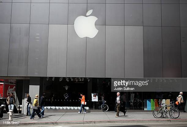 Pedestrians walk by an Apple Store following an announcement that Apple has become the world's most valuable brand on May 9 2011 in San Francisco...