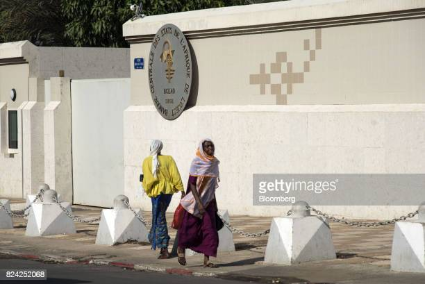 Pedestrians walk by an entrance to The Central Bank of West African States in the Plateau district of Dakar Senegal on Friday July 28 2017...