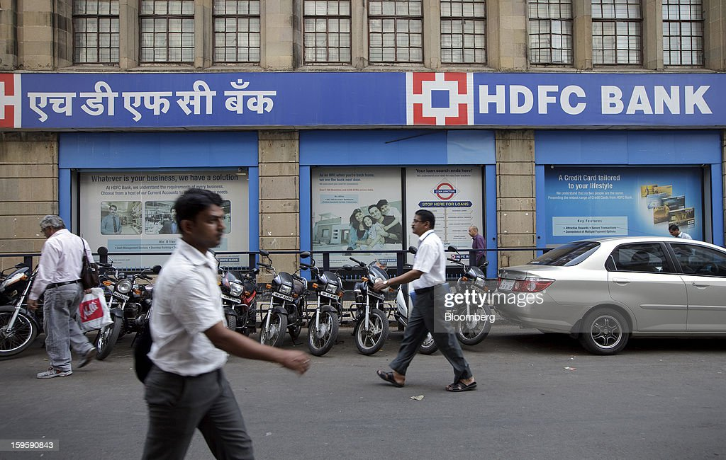 Pedestrians walk by an HDFC Bank Ltd. branch in Mumbai, India, on Wednesday, Jan. 16, 2013. India's financial system has been made vulnerable by a deterioration in bank assets and a lack of capital as the economy slowed, according to the International Monetary Fund. Photographer: Kuni Takahashi/Bloomberg via Getty Images