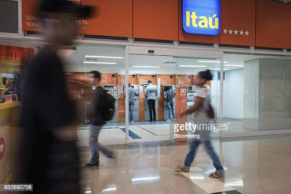 Pedestrians walk by as customers use automated teller machines at a Itau Unibanco Holding SA bank branch in Brasilia Brazil on Wednesday Jan 18 2017...