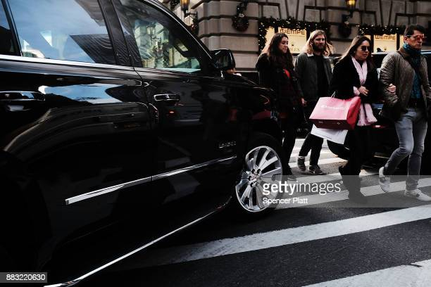 Pedestrians walk by luxury retailers along a Manhattan street on November 30 2017 in New York City Republicans are coming closer to getting the votes...
