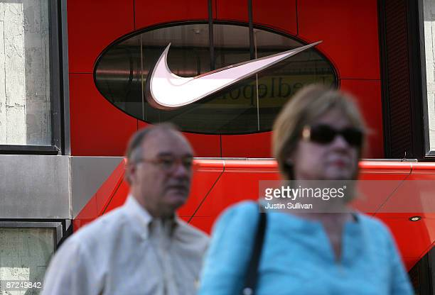 Pedestrians walk by the Nike 'swoosh' logo that is displayed on the exterior of a NikeTown store May 15 2009 in San Francisco California Athletic...