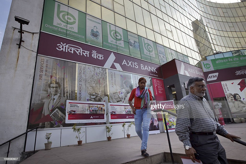 Pedestrians walk down a flight of stairs in front of an Axis Bank Ltd. branch in Mumbai, India, on Wednesday, Jan. 16, 2013. India's financial system has been made vulnerable by a deterioration in bank assets and a lack of capital as the economy slowed, according to the International Monetary Fund. Photographer: Kuni Takahashi/Bloomberg via Getty Images