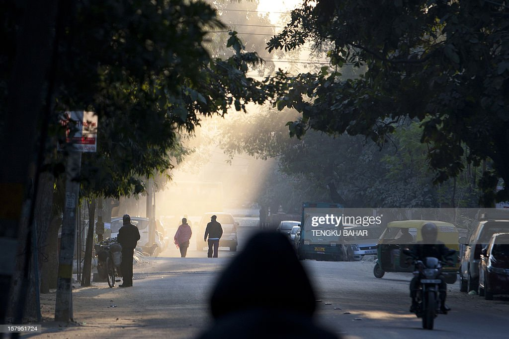 Pedestrians walk down a street as winter morning light filters through trees in New Delhi on December 8, 2012. India has long been criticised as one Asia's most inefficient bureaucracies, with its byzantine regulations and widespread corruption seen as a major deterrent to foreign investment. AFP PHOTO/TENGKU BAHAR
