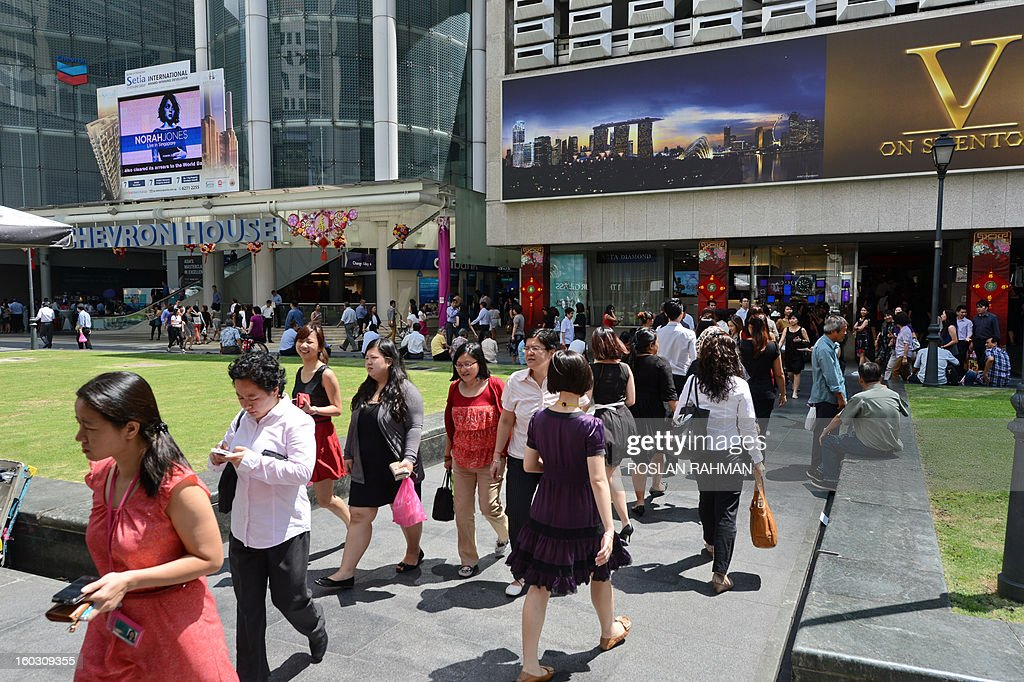 Pedestrians walk down a street in downtown financial district in Singapore on January 29, 2013. Singapore's population may reach almost seven million by 2030, up from 5.31 million currently, with the number of citizens shrinking to barely half of the total, the government said January 29.