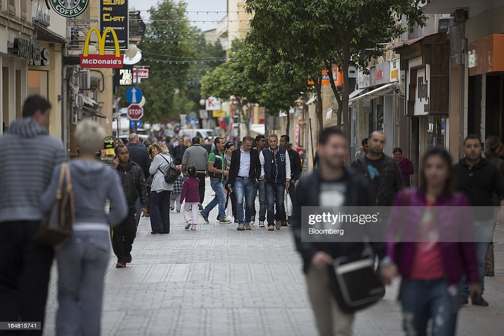 Pedestrians walk down Ledra Street in Nicosia, Cyprus, on Thursday, March 28, 2013. The Central Bank of Cyprus's capital controls will include a 300-euro ($383) daily limit on withdrawals and restrictions on transfers to accounts outside the country. Photographer: Simon Dawson/Bloomberg via Getty Images