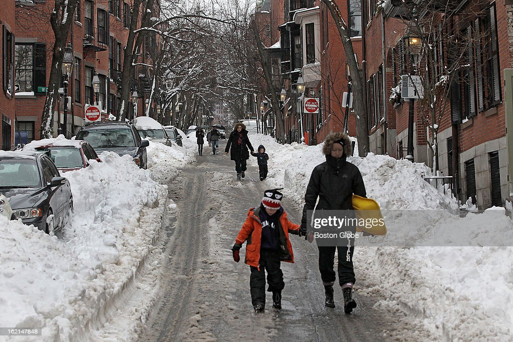 Pedestrians walk down the middle of Pickney Street on Beacon Hill instead of the sidewalks since the large piles of snow covering them haven't been cleared yet, after a blizzard hit New England.