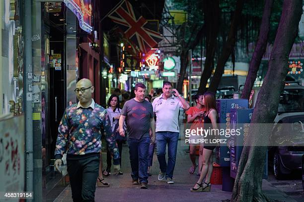 Pedestrians walk down the pavement past bars and restaurants in Hong Kong's Wanchai district on November 3 2014 A British banker appeared in a Hong...