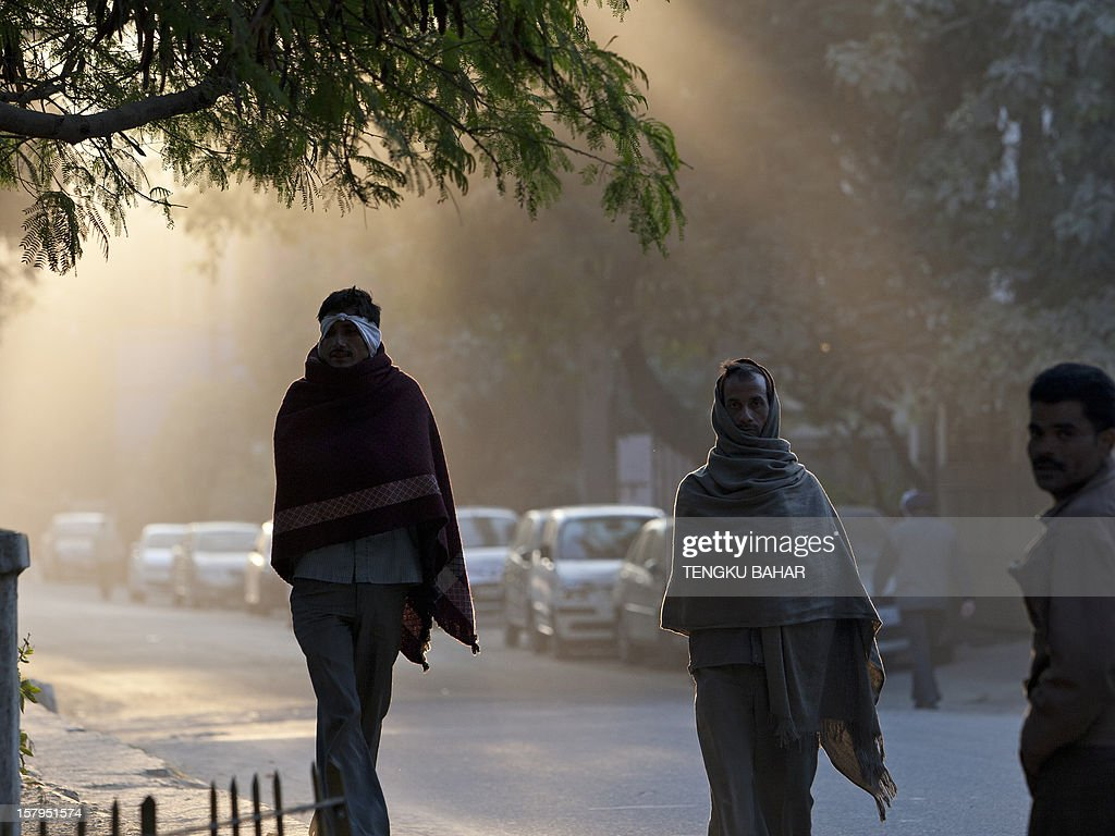 Pedestrians walk down the street as winter morning light filters through trees in New Delhi on December 8, 2012. India has long been criticised as one Asia's most inefficient bureaucracies, with its byzantine regulations and widespread corruption seen as a major deterrent to foreign investment. AFP PHOTO/TENGKU BAHAR