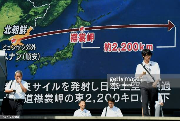 Pedestrians walk in front of a large video screen in Tokyo broadcasting a news report about North Korea's latest missile test that passed over Japan...