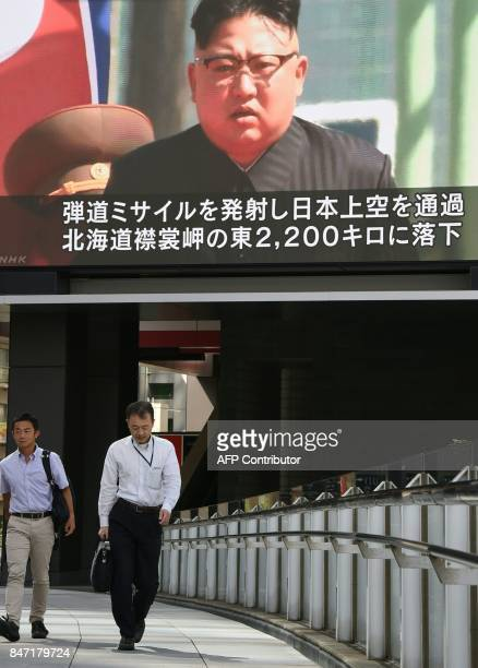 Pedestrians walk in front of a large video screen in Tokyo broadcasting a news report showing North Korean leader Kim JongUn following a North Korean...