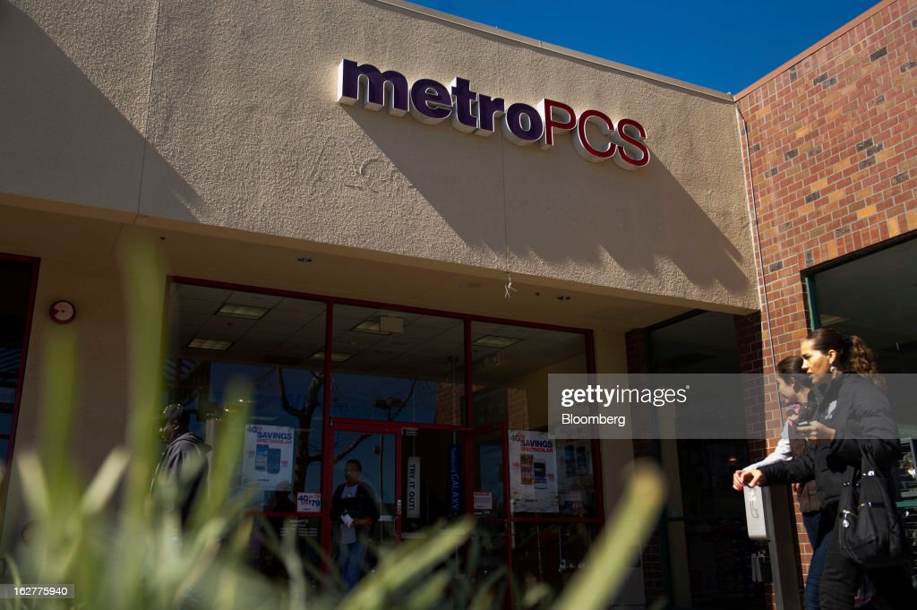 Pedestrians walk in front of a MetroPCS Communications Inc. store in Emeryville, California, U.S., on Tuesday, Feb. 26, 2013. MetroPCS Communications Inc. fourth-quarter revenue, released today, matches estimated earnings. Photographer: David Paul Morris/Bloomberg via Getty Images