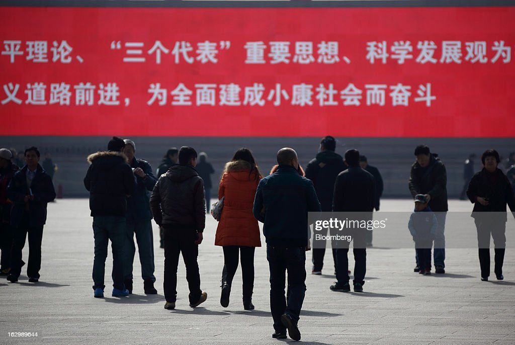 Pedestrians walk in front of a monitor displaying a slogan at Tiananmen Square in Beijing, China, on Sunday, March 3, 2013. Premier Wen Jiabao will this week formally announce this year's economic targets when he delivers his final work report to the National People's Congress, which begins on March 5. Photographer: Tomohiro Ohsumi/Bloomberg via Getty Images