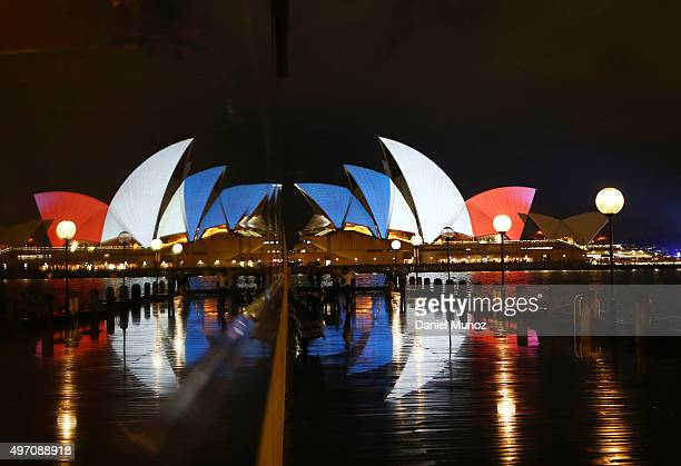 Pedestrians walk in front of a reflection of the Sydney Opera House as its sails are illuminated in the colours of the French flag on November 14...