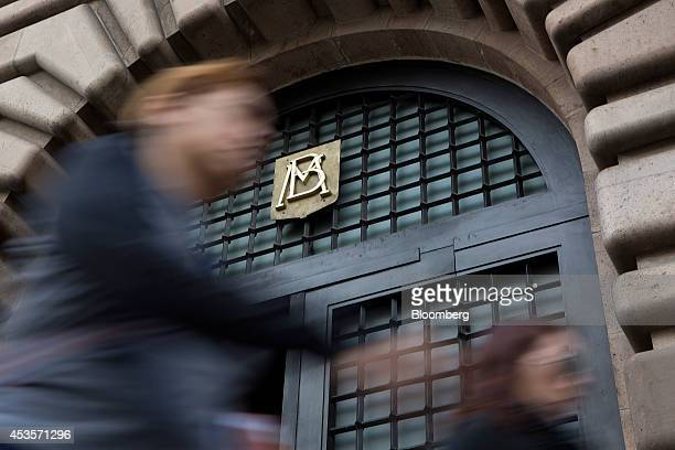 Pedestrians walk in front of the Banco de Mexico headquarters building in Mexico City Mexico on Wednesday Aug 13 2014 Mexican policy makers lowered...